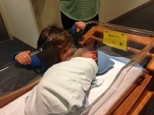 Big sister Etta gazes with awe and delight at her brand new sibling