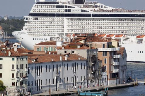 Gigantic cruise ship dwarfing the surrounding buildings
