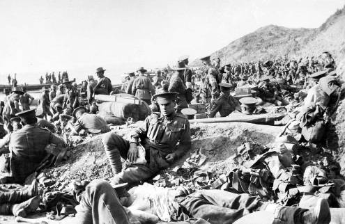 An Australian soldier lies wounded in the foreground, as hundreds of other soldiers move among the dead and wounded on the beach at Anzac Cove on the day of the landing. The soldiers wearing Red Cross armbands are tending to the wounded. Boxes of equipment are stacked among the men and the beach is also littered with discarded personal equipment. This scene is looking along the beach to the north. Photograph by Charles Atkins. [AWM PS1659]